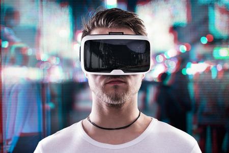 Homem que desgasta óculos de realidade virtual contra iluminado da noite da cidade