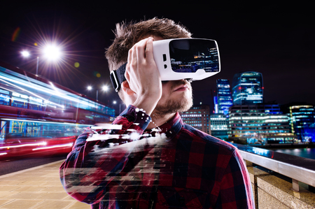 Double exposure of man wearing virtual reality goggles and night city Foto de archivo