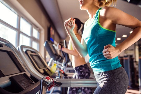 モダンなジムでトレッドミルをスポーツ服で走っている女性に合う 2 つの魅力的です 写真素材