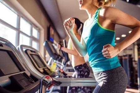 Hai phụ nữ hấp dẫn phù hợp chạy trong bộ quần áo thể thao trên máy tập chạy bộ ở phòng tập thể dục hiện đại