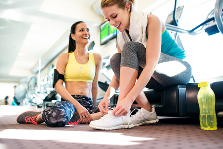 active listening: Two attractive fit women in a gym getting ready for workout, tying shoelaces on sport shoes, close up of legs