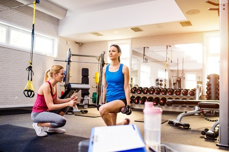 work out: Gym, woman with personal trainer exercising squats, detail of clipboard with work out plan, water bottle Stock Photo