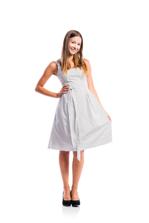 Standing teenage girl in black-and-white dotted dress, heels, studio shot, young woman, isolated on white background Banque d'images