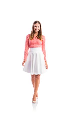 falda: De pie adolescente en la parte superior de encaje de color rosa y elegante falda blanca, zapatos de tacón, tiro del estudio, mujer joven, aislado en fondo blanco Foto de archivo