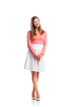 legs crossed: Standing teenage girl in pink lace top and elegant white skirt, heels, legs crossed, studio shot, young woman, isolated on white background