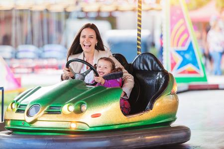 Niña linda con su madre que se divierte en parque de atracciones, conduciendo un auto de choque, el parque de atracciones
