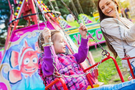 chain swing ride: Cute little girl with her mother enjoying time at fun fair, chain swing ride, amusement park