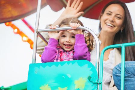Симпатичная маленькая девочка с ее матерью, наслаждаясь время на веселой ярмарке, парк аттракционов