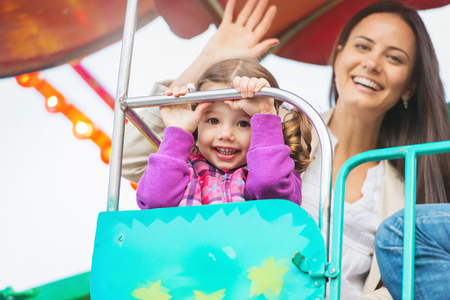 Cute little girl with her mother enjoying time at fun fair, amusement park Stock Photo