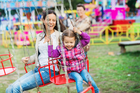 theme parks: Cute little girl with her mother having fun at fun fair, chain swing ride, amusement park Stock Photo