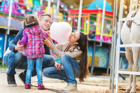 carnival ride: Family with daughter, amusement park, mother eating cotton candy, fun fair Stock Photo