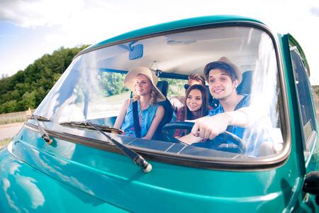 nene y nena: niño inconformista conduciendo una vieja autocaravana con amigos adolescentes, roadtrip, día soleado de verano Foto de archivo