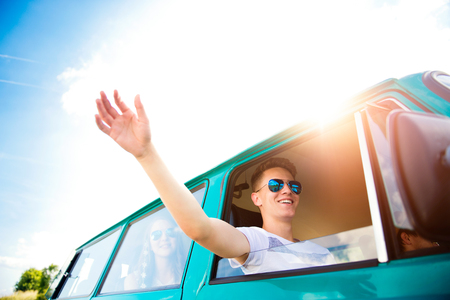 roadtrip: Teenagers inside an old campervan on a roadtrip, boy  stretching hand out of window, sunny summer day Stock Photo