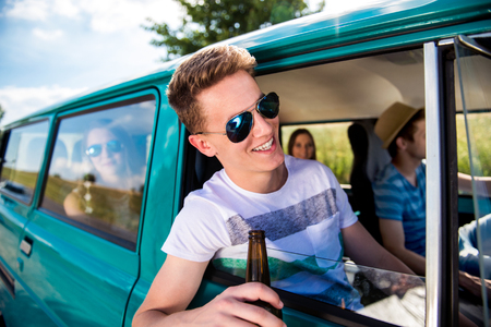 cars on the road: Teenagers inside an old campervan on a roadtrip, boy leaning out of window, drinking beer, sunny summer day Stock Photo