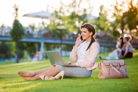 美しい若い実業家昼休み、公園の芝生の上に座っている彼女のスマート フォン, 日当たりの良い夏の日にチェックします。
