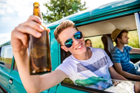 roadtrip: Teenagers inside an old campervan on a roadtrip, boy leaning out of window, drinking beer, sunny summer day Stock Photo