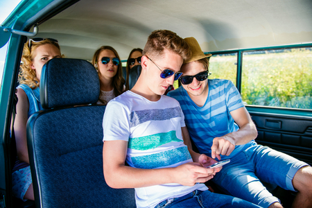 roadtrip: Teenage boys and girls inside an old campervan, playing with smart phone, roadtrip, sunny summer day