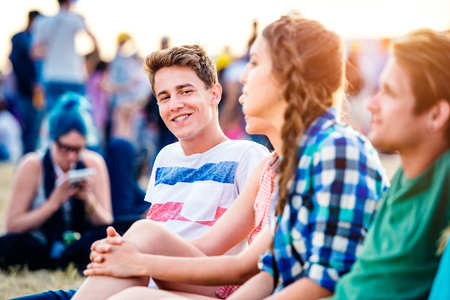 party friends: Group of teenagers at summer music festival, sitting on the ground , hipster boy in striped t-shirt