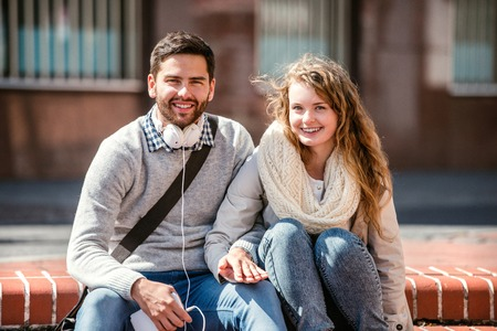 busy beard: Young couple in love in town sitting on stairs, holding hands