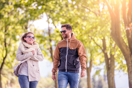 walk in: Smiling couple in love  in autumn sunny nature on a walk,  against green trees
