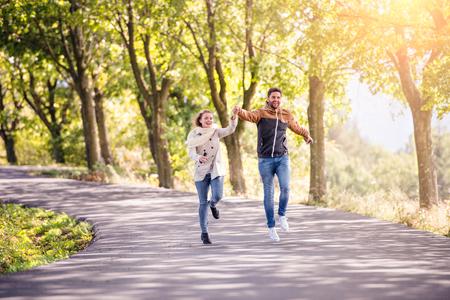 caminar: Sonriente pareja de enamorados en la naturaleza soleado de otoño en una caminata, correr, tomados de la mano, contra los árboles verdes