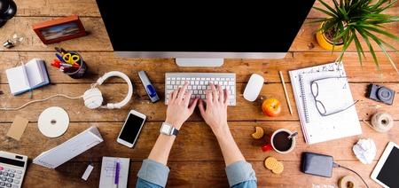 Bedrijfs persoon die bij bureau werkt. Smart horloge op de hand en slimme telefoon op de tafel. Kopje koffie, blocnote en een bril en diverse kantoorartikelen rond de werkplek. Plat.