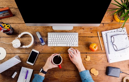 hand lay: Business person working at office desk. Smart watch on hand and smart phone on the table. Coffee cup, notepad and glasses and various office supplies around the workplace. Flat lay.