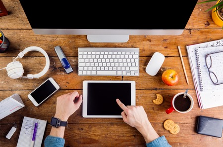 hand lay: Business person at office desk working on tablet. Smart watch on hand and smart phone on the table. Coffee cup, notepad and glasses and various office supplies around the workplace. Flat lay. Stock Photo