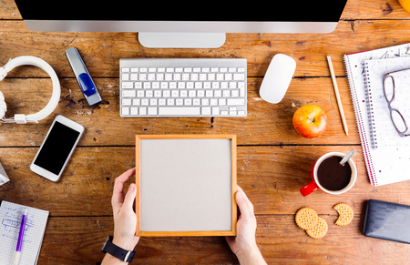 hand lay: Business person working at office desk. Holding picture frame. Smart watch on hand and smart phone on the table. Copy space. Flat lay.