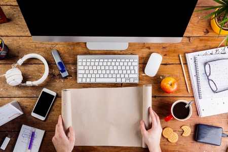 working on computer: Business person working at office desk. Holding paper roll. Smart phone on the table. Copy space. Flat lay. Stock Photo