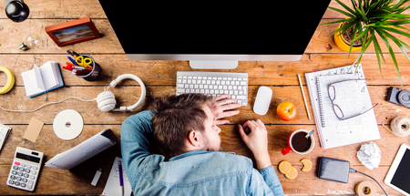sleeping tablets: Businessman sleeping on the desk.  Coffee cup, notepad, glasses and various office supplies around the workplace. Flat lay. Stock Photo