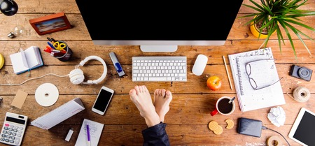 phone business: Businessman working in his office with feet on desk. Smart phone, tablet and various office supplies around the workplace. Flat lay.