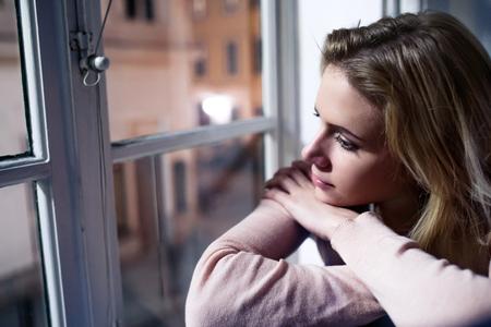 窓の外を見て、夜に窓の下枠の上に座って美しいブロンド女性 写真素材