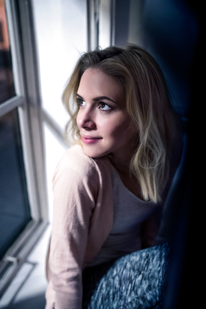sill: Beautiful blond woman sitting on window sill at night, looking out of window