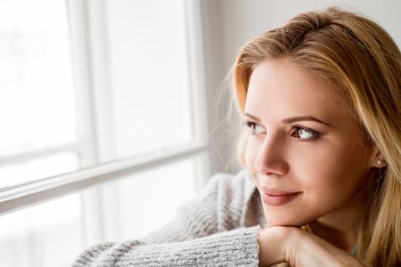 A mulher loura bonita senta-se no peitoril da janela, olhando para fora da janela
