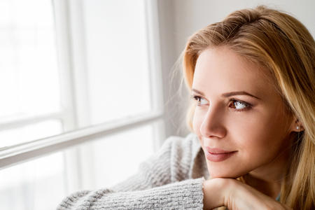 Güzel sarışın bir kadın, pencere pervazına oturmuş pencereden dışarı bakıyor Stok Fotoğraf