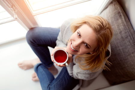sill: Beautiful blond woman sitting on window sill holding a cup of tea, high angle view Stock Photo