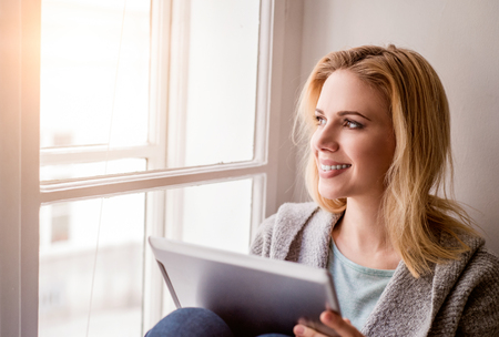 sill: Beautiful blond woman with tablet sitting on window sill, sunny day