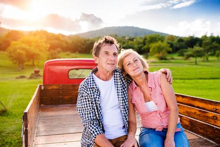 detras de: Pareja de ancianos sentados en la parte trasera de la camioneta roja de la vendimia, abrazando, naturaleza verde soleado
