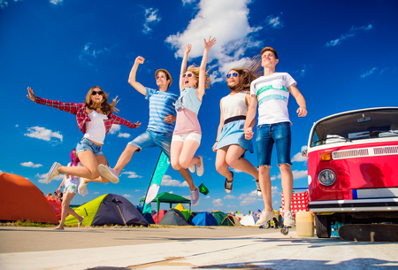 Group of teenage boys and girls at summer music festival jumping by vintage red campervan