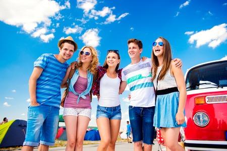 campervan: Group of teenage boys and girls at summer music festival posing by vintage red campervan