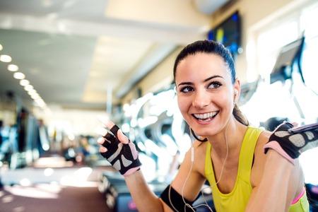 la mujer del ajuste atractivo en una sesión de gimnasio, descansar, contra una fila de cintas de correr