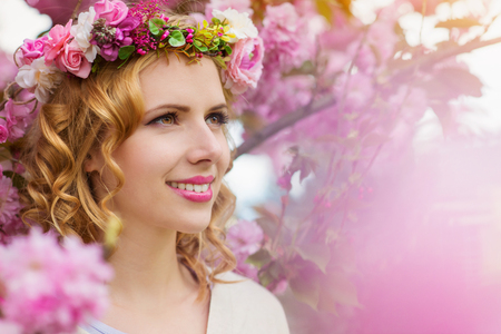 flower head: Smiling woman with blond hair with flower wreath against pink tree in blossoom, spring nature