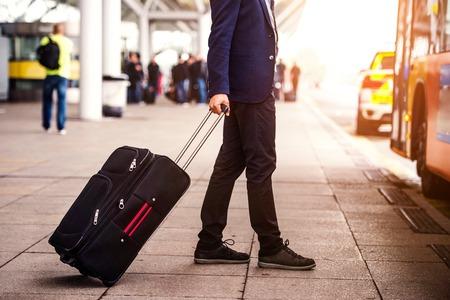 Nierozpoznany biznesmen z bagażem czeka na lotnisku, zamierza wejść do autobusu, słoneczny dzień Zdjęcie Seryjne