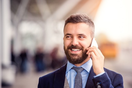Hipster businessman in suit making a phone call, waiting at the airport, sunny day Imagens