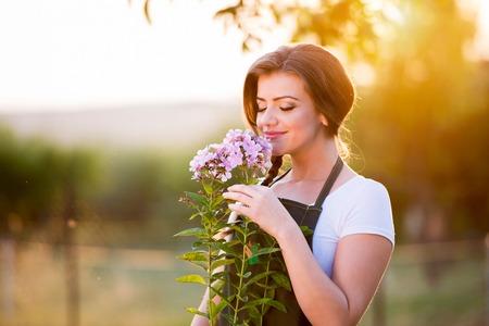 Jardinero joven en su jardín que huele las flores, naturaleza verde soleado al atardecer Foto de archivo