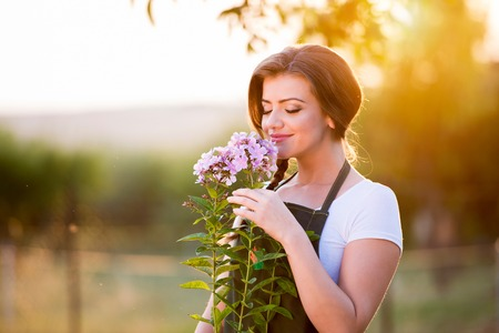 Young gardener in her garden smelling flowers, green sunny nature at sunset Imagens