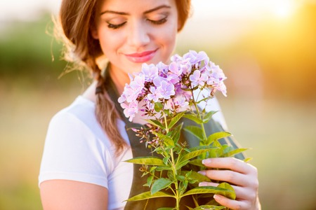 Young gardener in her garden holding flowers, green sunny nature at sunset Stock Photo