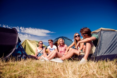 sitting on the ground: Group of teenage boys and girls at summer music festival, sitting on the ground in front of tents Stock Photo