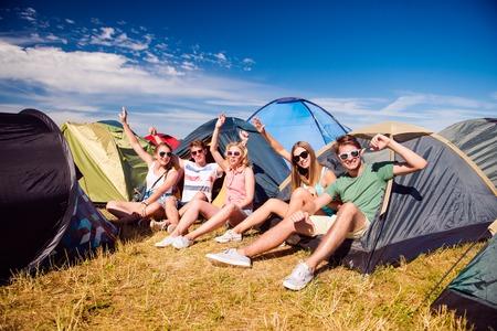 Groep van tiener jongens en meisjes in de zomer muziekfestival, zittend op de grond voor tenten Stockfoto